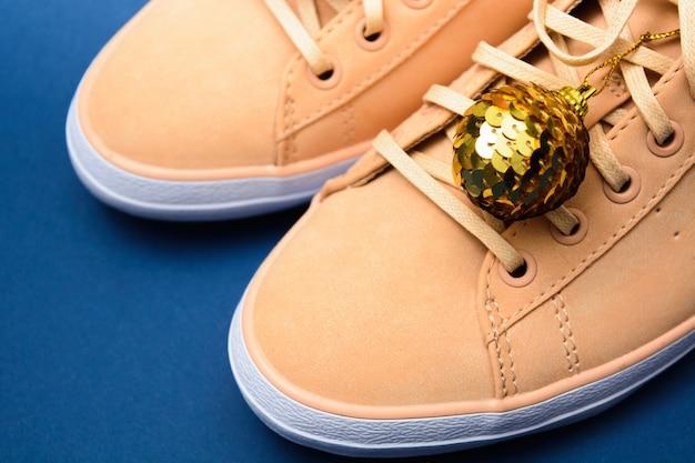 金色のクリスマス飾りが付いたベージュのスニーカー