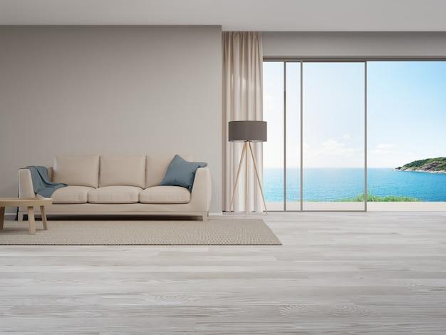 Бежевый диван у глухой стены на пустом деревянном полу большой гостиной в современном доме