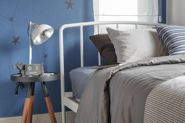 Beige and striped pillow on modern style bed setting and the blu