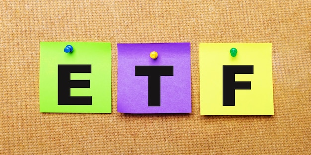 On a beige surface, multi-colored stickers for notes with the word etf exchange traded funds