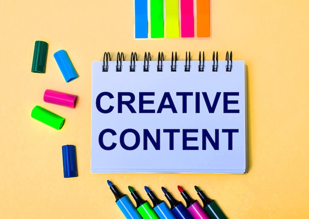 On a beige surface, a notebook with the words creative content, bright felttip pens and stickers