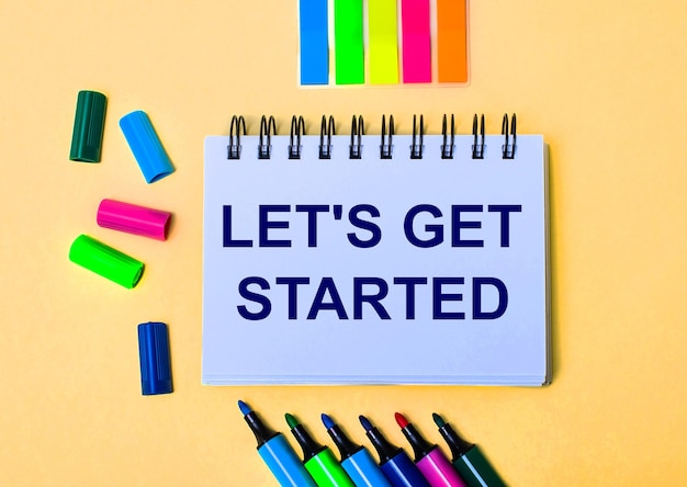 On a beige surface, a notebook with the words let is get started, bright felt-tip pens and stickers