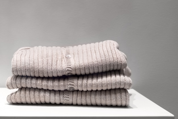 Beige sweaters made from natural fabrics are folded on the table