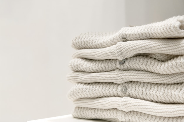Beige sweaters made from natural fabrics are folded on the table.