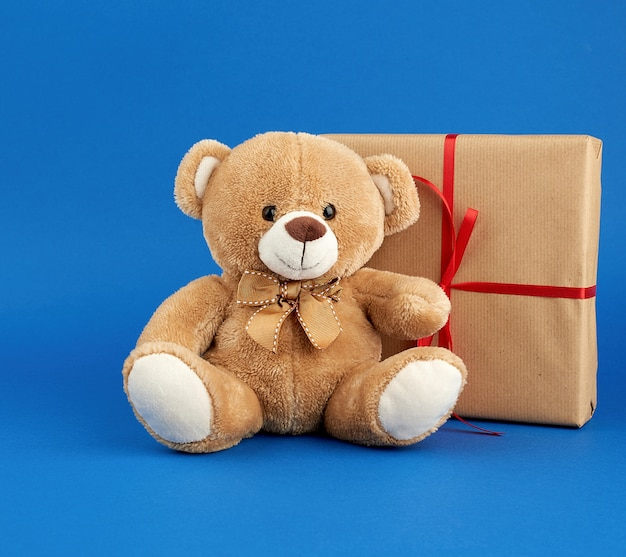 Beige teddy bear and a box wrapped in brown kraft paper and tied with a red ribbon