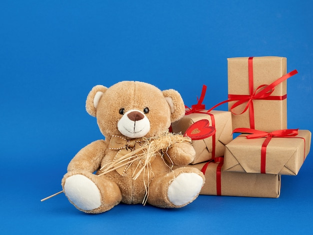 Beige teddy bear and a stack of boxes wrapped in brown kraft paper and tied with a red ribbon