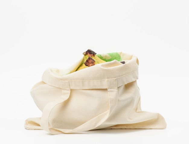 Beige textile bag with fresh fruits on a white surface, zero wast