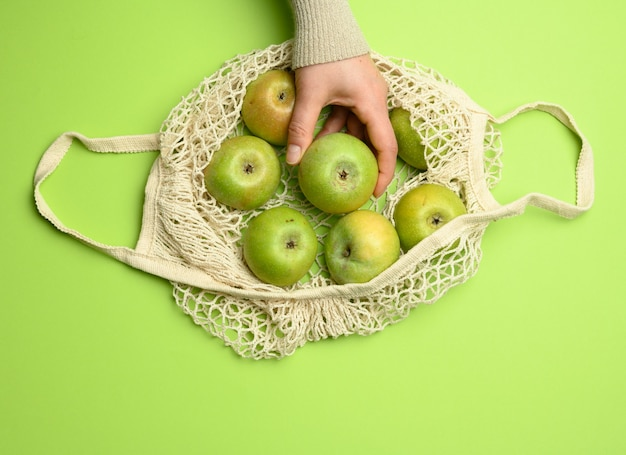 Beige textile bag with green apples on a green background, the concept of reusable things, zero waste