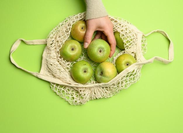 녹색 배경에 녹색 사과가 달린 베이지 색 섬유 가방, 재사용 가능한 물건의 개념, 폐기물 제로
