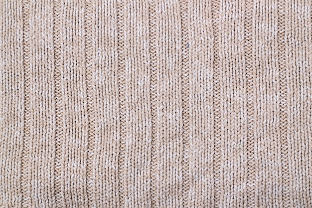 Beige texture of knitted wool sweater. hand knitting. knit and purl stitch pattern