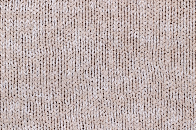 Beige texture of knitted wool sweater. hand knitting.