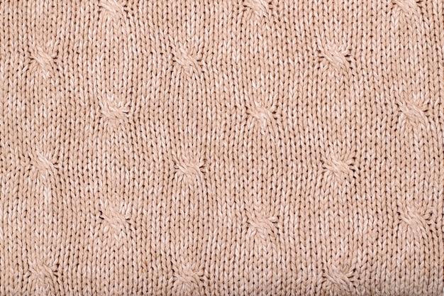 ニットウールセーターのベージュの風合い。手編み。細長いステッチパターン