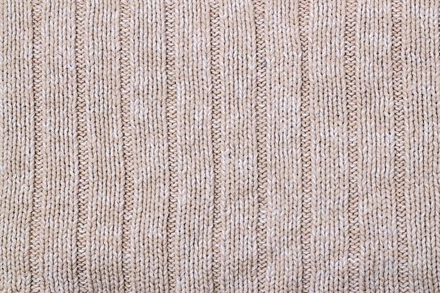 ニットウールセーターのベージュの風合い。手編み。ニットとプルのステッチパターン