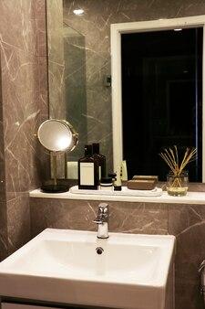 ベージュトーンの大理石の壁は、白い洗面台と小さなカウンターと一致しています