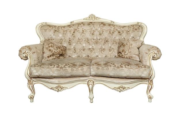 白い背景の上に分離されたソファ枕とベージュの房状のレトロなチェスターフィールドスタイルのソファ
