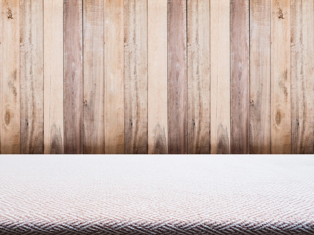 Beige tweed fabric tablecloth and wooden background