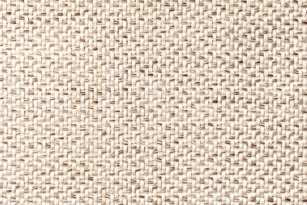 Beige vintage fabric with woven texture closeup. textile macro background