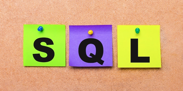 On a beige wall, multi-colored stickers for notes with the word sql