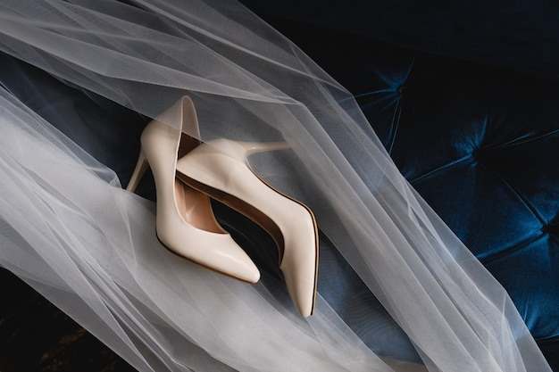 Beige wedding bridesmaid shoes on the velour sofa, tulle or veil. modern women's shoes.
