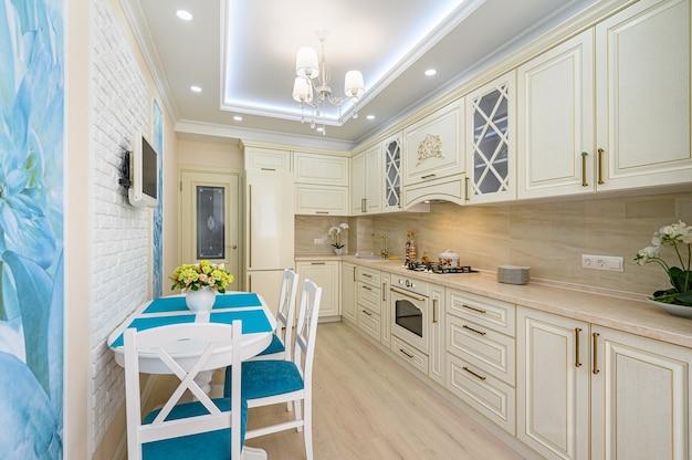 Бежевая, белая и голубая современная классическая кухня в стиле прованс, вся мебель с открытыми дверцами и ящиками.