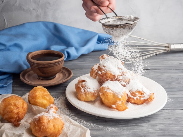 Beignet sprinkled with icing sugar on a wooden table with coffee.