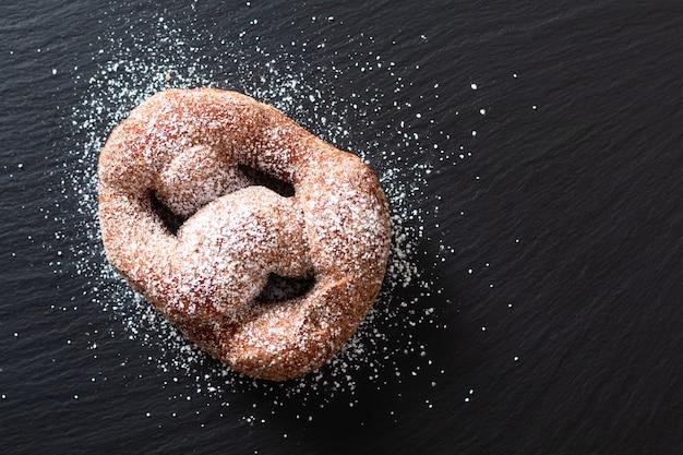 食品コンセプトシングルbeignetフランス酵母ドーナツ揚げ黒スレートボード上のシュー菓子
