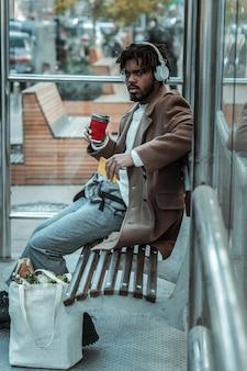 怒っている。セミポジションに座ってバス停に座っているハンサムなひげを生やした男
