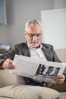 집에있다. 매력적인 성숙한 남자 신문을 들고 집에있는 동안 웃고