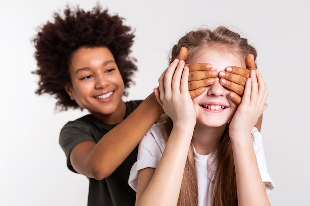 С завязанными глазами. по-детски темноволосый мальчик ковыляет и играет со своим другом, пока она прикасается к нему