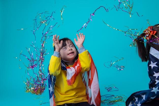함께 평온함. 다운 증후군이있는 행복한 어린 소녀가 공중에 컬러 리본을 던지고 재미