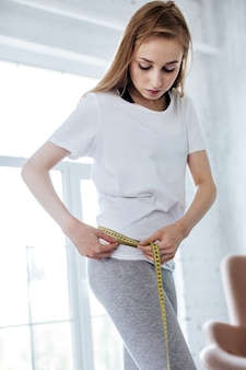 Being on diet. unsmiling thing woman measuring her waist and wearing home clothes