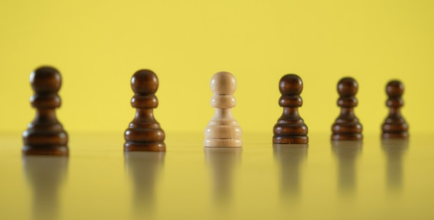 Being different and thinking outside the box concept. white pawn among black pawns, selective focus.