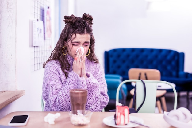 Being extremely sentimental. sick dark-haired girl blowing out snot in napkin while sitting in cafe with flu