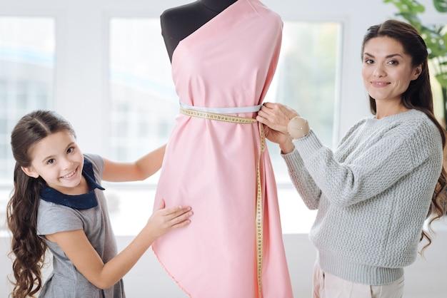 ファッショナブルであること。ドレスの母親の近くに立って、服をデザインしながらいくつかの測定を行う喜んでスマートな素敵な女性