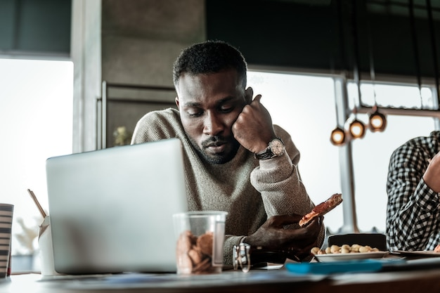 Being frustrated. concentrated bearded male bowing head while looking at keyboard of his laptop
