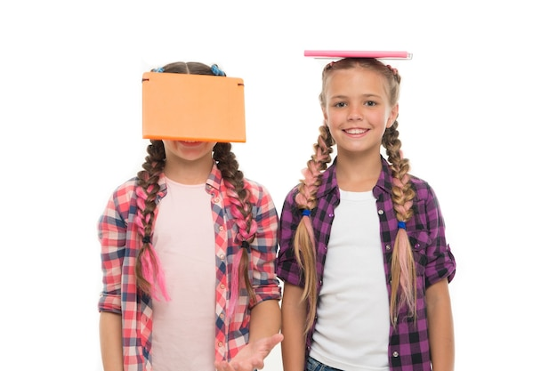 Being genius for hard study. genius schoolchildren isolated on white. small girls holding books on heads with genius ideas. the brightest young minds or genius.