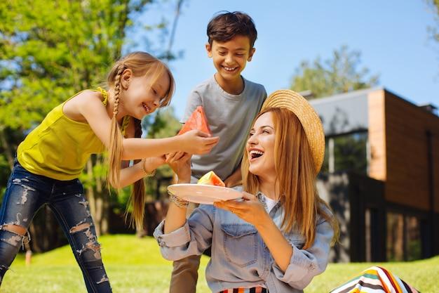 행복하다. 콘텐츠 젊은 어머니가 웃고 그녀의 아이들에게 수박을주는