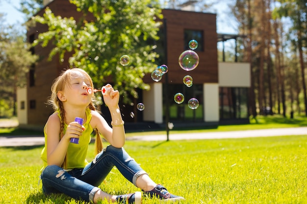 Being on holidays. happy charming girl sitting on the ground and blowing soap bubbles
