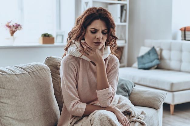 아프다. 집에서 소파에 앉아있는 동안 담요 기침으로 덮여 아픈 젊은 여성