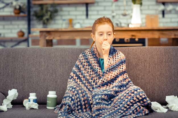 Being ill. unhappy sick girl being covered with plaid while suffering from an illness