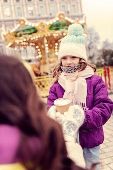 모든 귀에 있습니다. 부모와 함께 밖에있는 동안 따뜻한 모자를 쓰고 귀여운 작은 여성