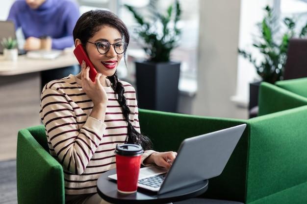 すべての耳にいる。コンピューターで働いている間電話で話している喜んでいる女性