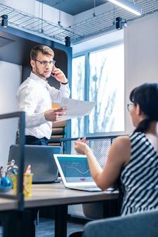 すべての耳にいる。同僚に説明しながら右手に書類を持っている真面目な男性