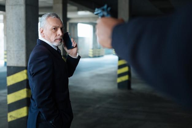 В опасности. несчастный обеспокоенный приятный мужчина смотрит на пистолет и звонит, находясь под прицелом