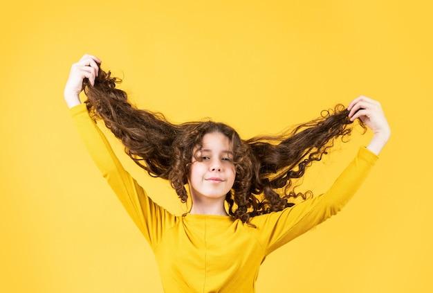 재미있는 분위기에 있습니다. 건강하고 강한 모발. 좋은 샴푸나 로션. 미용실 미용실. 강하고 건강한 머리 개념. 작은 아이 긴 머리. 장난. 긴 바람이 부는 머리를 가진 행복한 소녀.