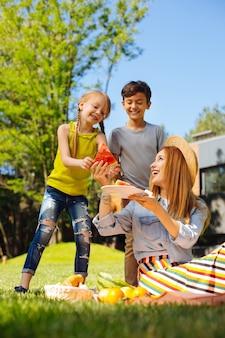 영감 받기. 미소하고 그녀의 아이들에게 수박을주는 젊은 어머니 경고