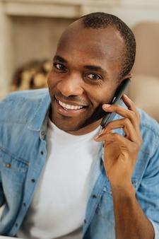 うれしそうに。ニヤリと電話で話し、カムを覗き込んでいる見栄えの良い陽気な暗い目のアフリカ系アメリカ人の男