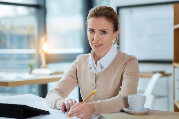 Занятость. крупным планом умелый дизайнер сидит за столом, работая над новыми проектами и выражая оптимизм