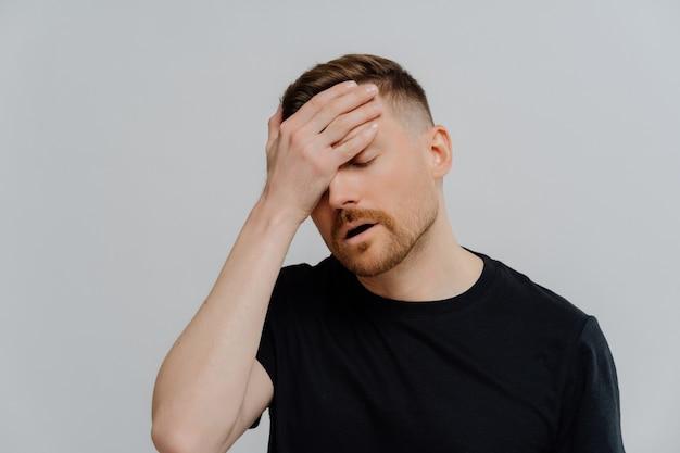 Переутомление. молодой усталый недовольный рыжий мужчина в черной рубашке с закрытыми глазами страдает от головной боли или миргена после тяжелого рабочего дня, прикладывает лоб и чувствует себя больным