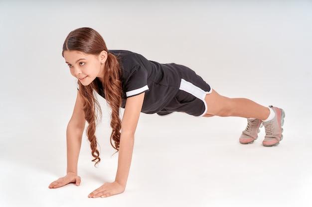판자에 서 있는 운동복을 입은 귀엽고 행복한 10대 소녀의 신체 활동 전체 길이